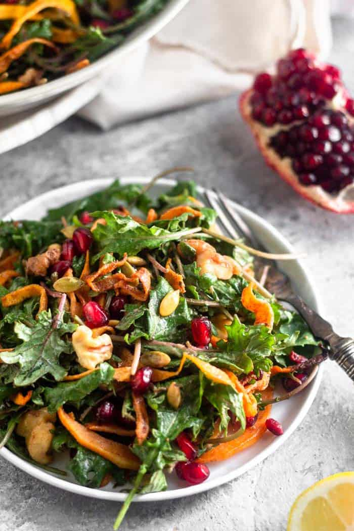 Small plate filled with a vegan kale salad with butternut squash and pomegranates. A fork is hanging off the side and behind it is a large bowl of salad and a quarter of an opened pomegranate.