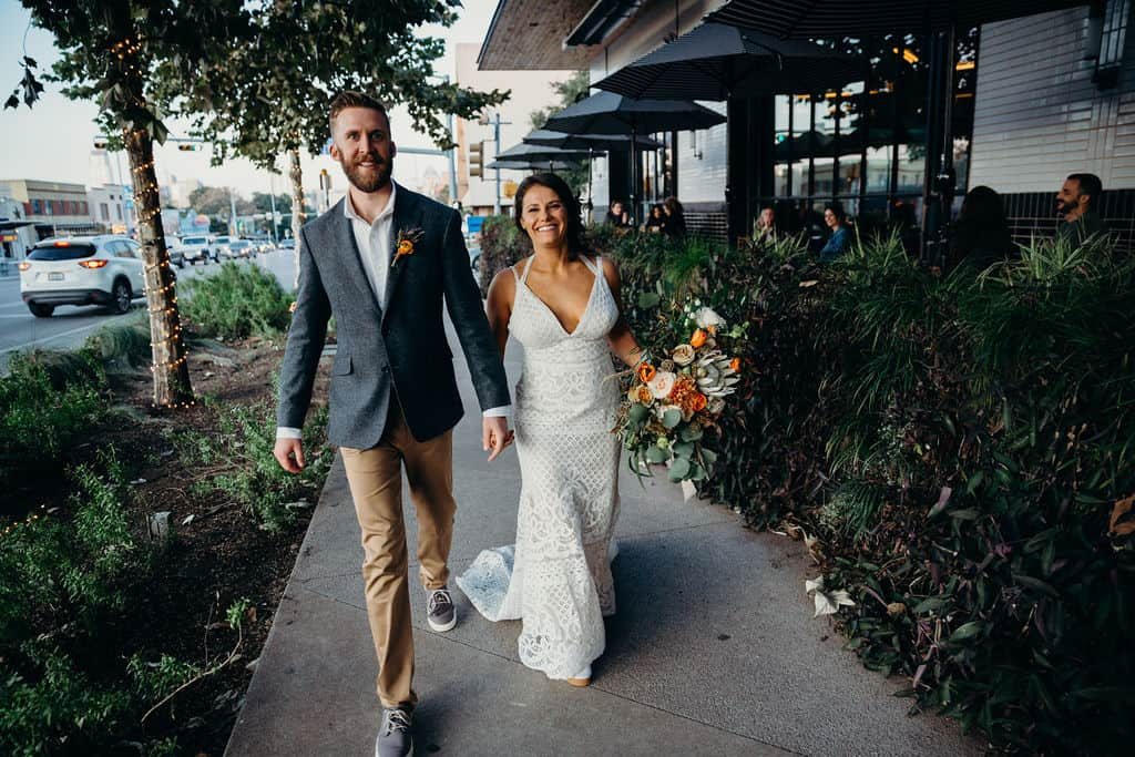 Married couple with the bride holding her bouquet walking down the street on a sidewalk