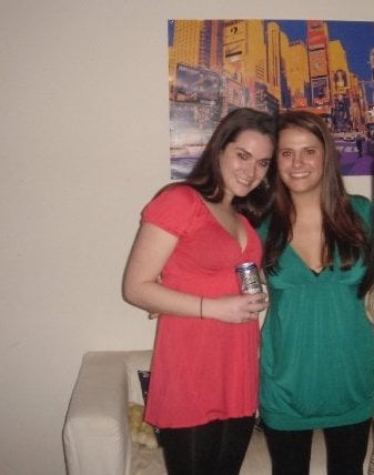 Two girls in an apartment. One wearing a green shirt, one wearing a red shirt and holding a beer