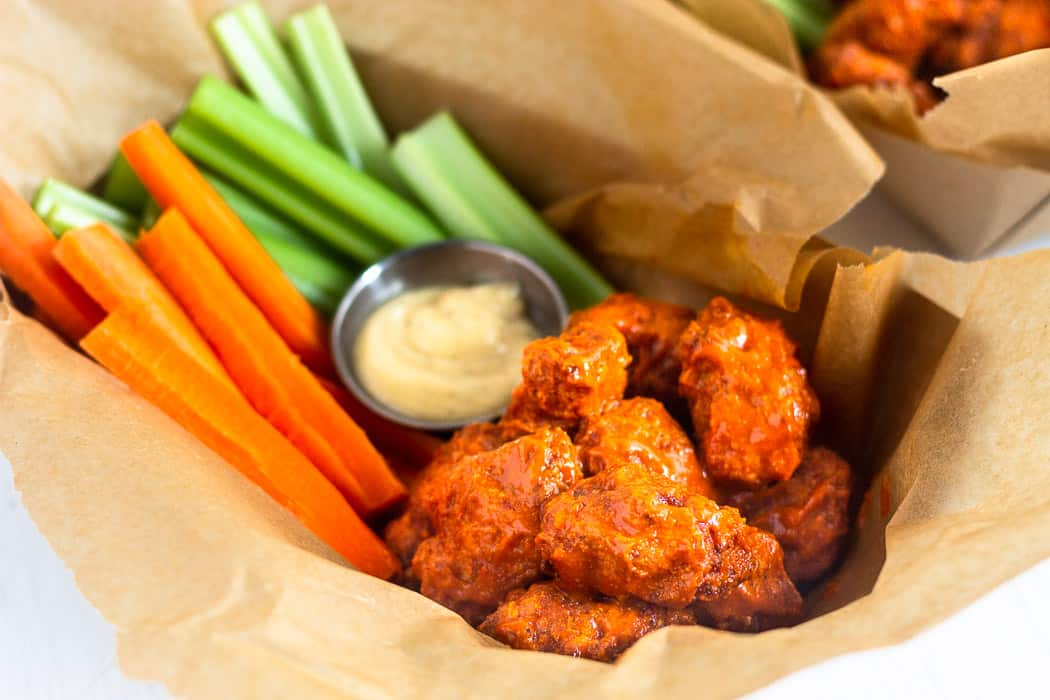 Close up of a basket of air fryer boneless buffalo wings with carrots, celery, and a side of ranch dressing.