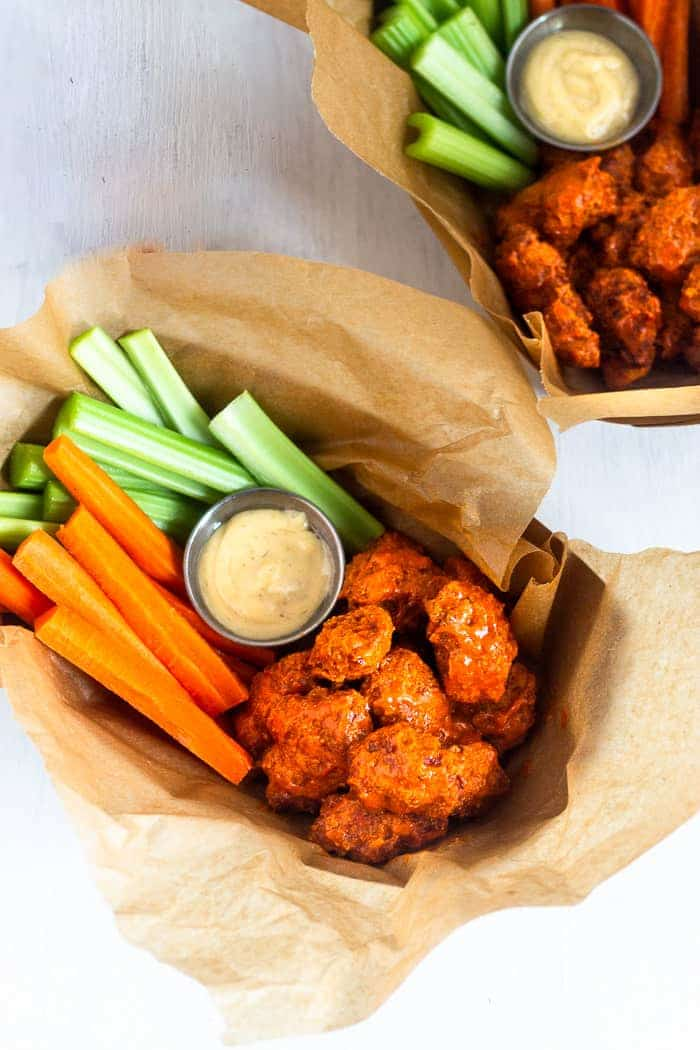 Overhead shot of two brown paper baskets filled with air fryer boneless buffalo wings, carrot sticks, celery sticks, and ranch dressing.