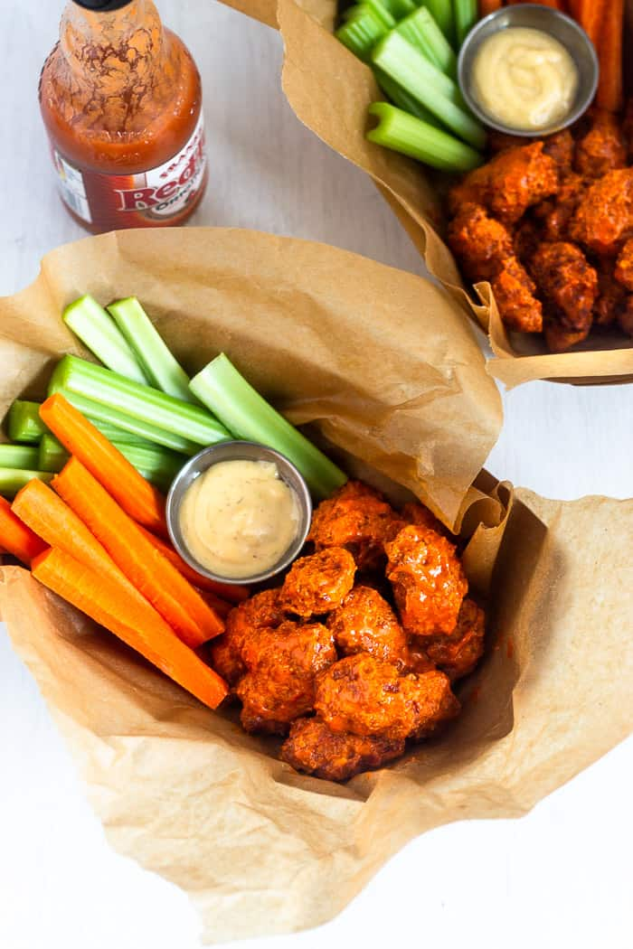 Overhead shot of two brown paper baskets filled with air fryer boneless buffalo wings, carrot sticks, celery sticks, and ranch dressing. Next to them is a bottle of Frank's red hot.