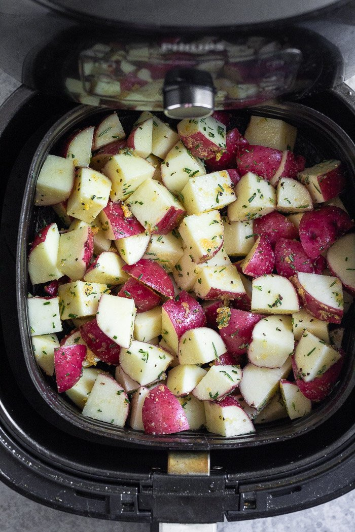 Diced raw potatoes in an air fryer basket.