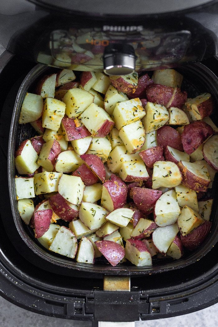 Halfway cooked diced red potatoes in an air fryer basket.