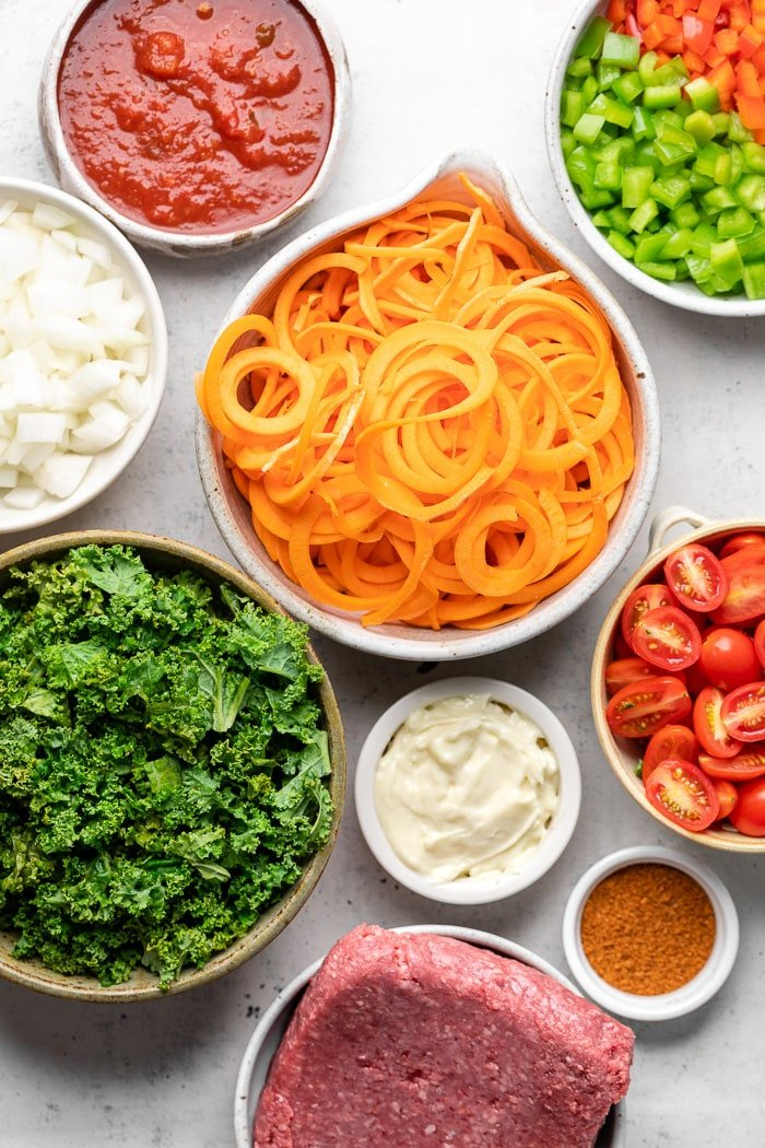 Overhead shot of a bowl with salsa, bowl with chopped peppers, bowl of sweet potato noodles, bowl of diced tomatoes, bowl of raw ground beef, bowl of chopped kale, bowl of diced onion, bowl of mayo, and bowl of taco seasoning.