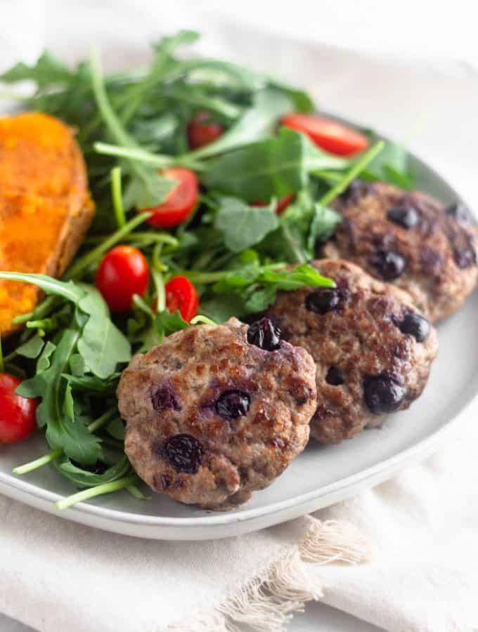 A white plate with half a sweet potato, fresh salad with cherry tomatoes, and 3 homemade paleo blueberry breakfast sausages.