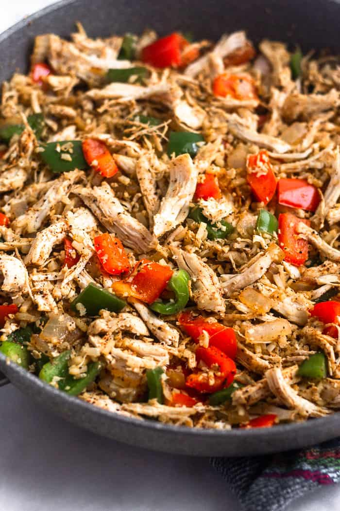 Large sauté pan filled with sautéed onion, peppers, cauliflower rice, and shredded chicken.