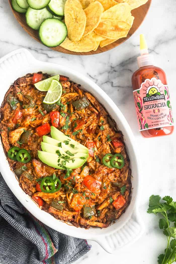 Overhead shot of baked spicy chicken enchilada dip in a large white casserole dish. It is garnished with avocado, lime wedges, jalapeño, and cilantro. Next to it is a bottle of sriracha, a plate of chips and cucumber, cilantro, and a blue towel.