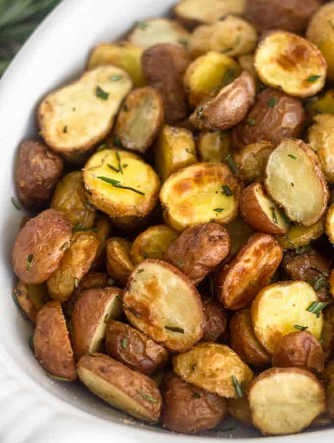 Close up of air fryer crispy garlic rosemary potatoes in a white casserole dish.