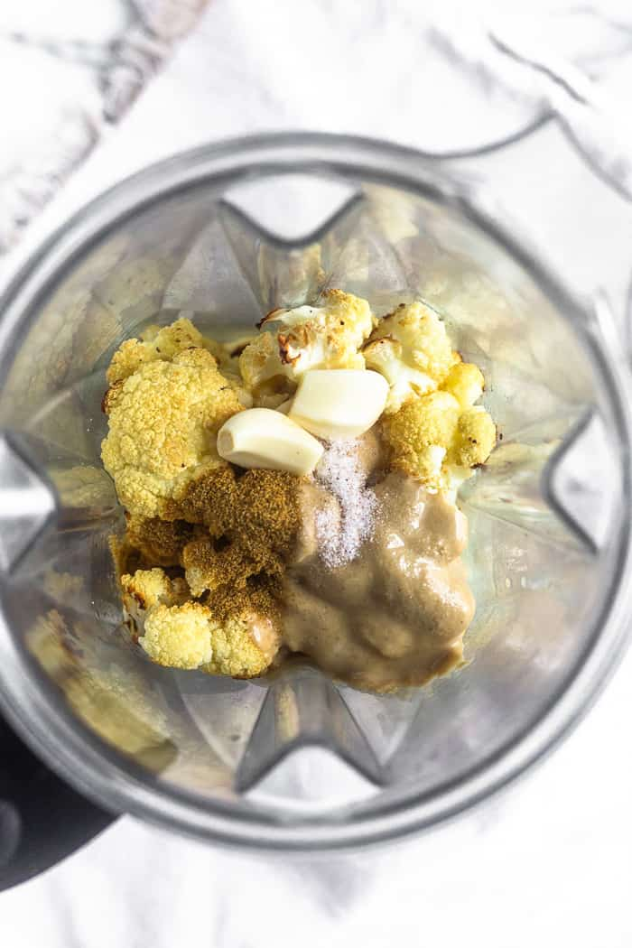 A blender filled with the ingredients of paleo cauliflower hummus - roasted cauliflower, tahini, garlic, cumin, and lemon juice.