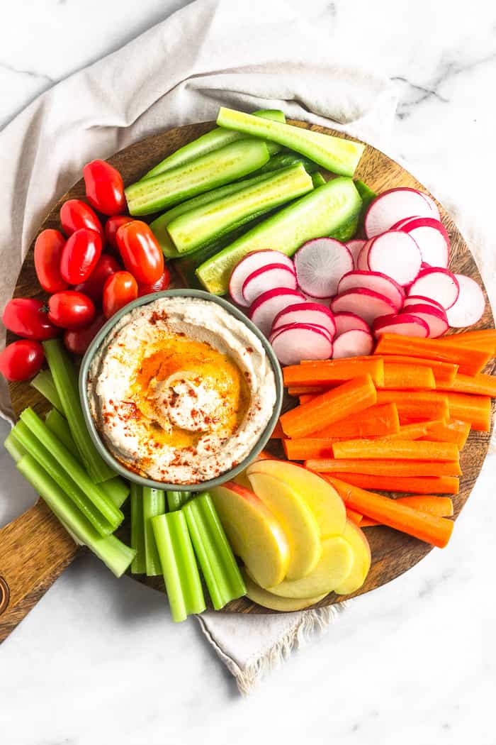 Large wooden platter filled with fresh cut veggies and fruit. In the middle is a bowl of paleo cauliflower hummus drizzled with olive oil and paprika.