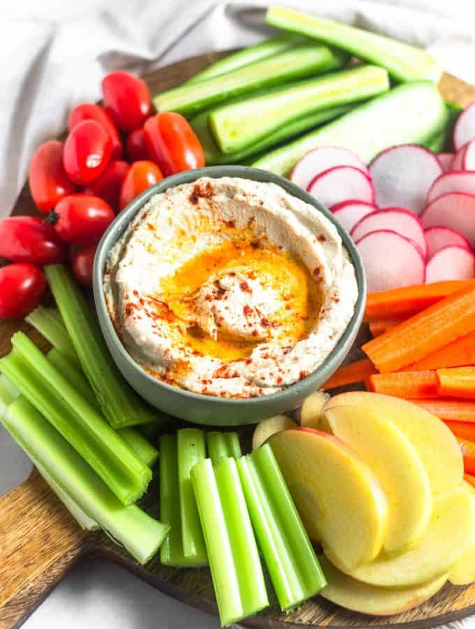 A circular wooden cutting board filled with a bowl of roasted cauliflower hummus surrounded by a bunch of fresh cut fruits and veggies.