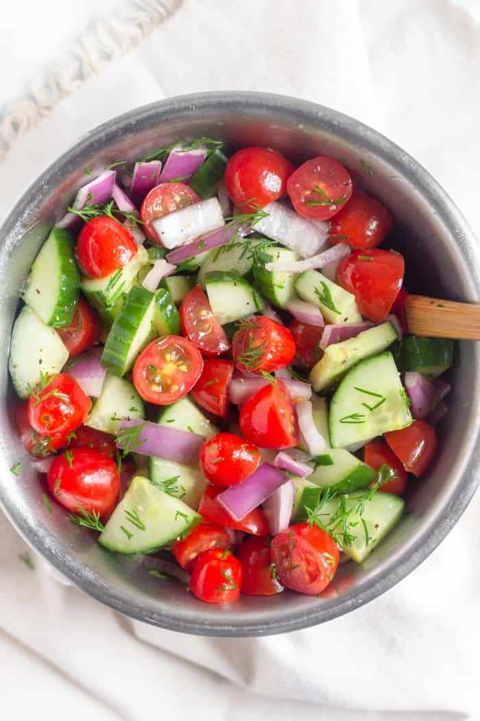 Bowl of chopped cucumbers, halved cherry tomatoes, chopped red onion, and fresh dill.