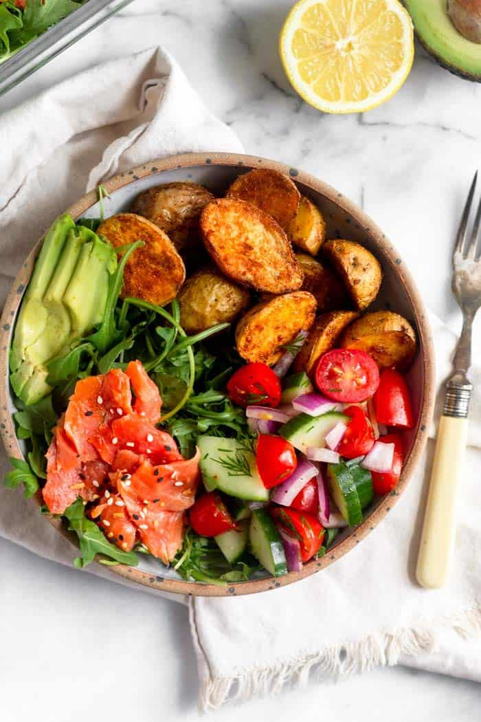 Meal prep smoked salmon breakfast bowl - arugula, smoked salmon, avocado, crispy potatoes, and tomato and cucumber salad in a bowl with a fork next to it. Next to it is half an avocado and a half a lemon.