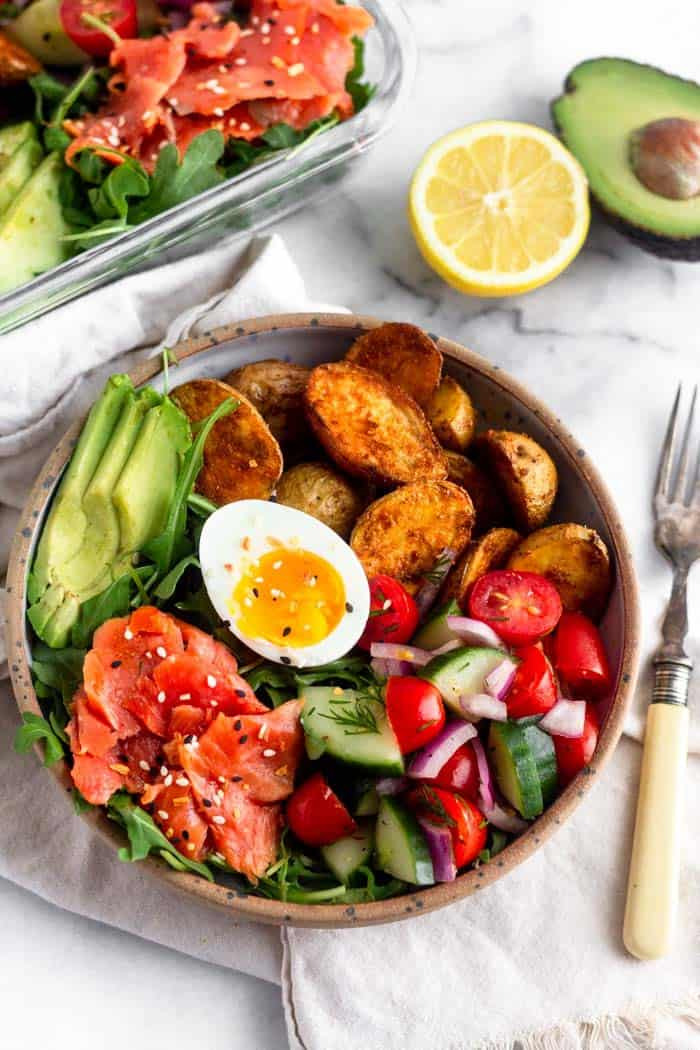 Overhead of a bowl filled with smoked salmon, half a jammy egg, avocado, roasted potatoes, tomato and cucumber salad, and greens. Next to it is at the same thing in a meal prep bowl along with half a lemon, half an avocado, and a fork.