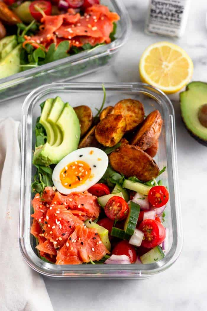Meal prep smoked salmon breakfast bowl filled with arugula, smoked salmon, tomato and cucumber salad, roasted potatoes, avocado, and half of a 6 minute jammy egg.