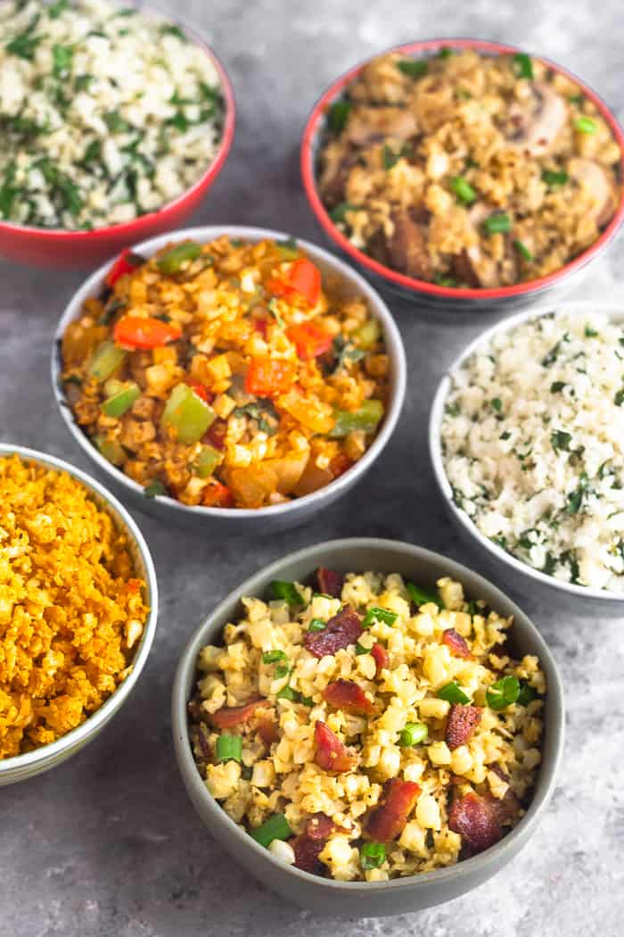 Six different bowls of cauliflower rice on a grey surface. Picture is shot at a 45 degree angle where the front is in focus and the back is blurred.