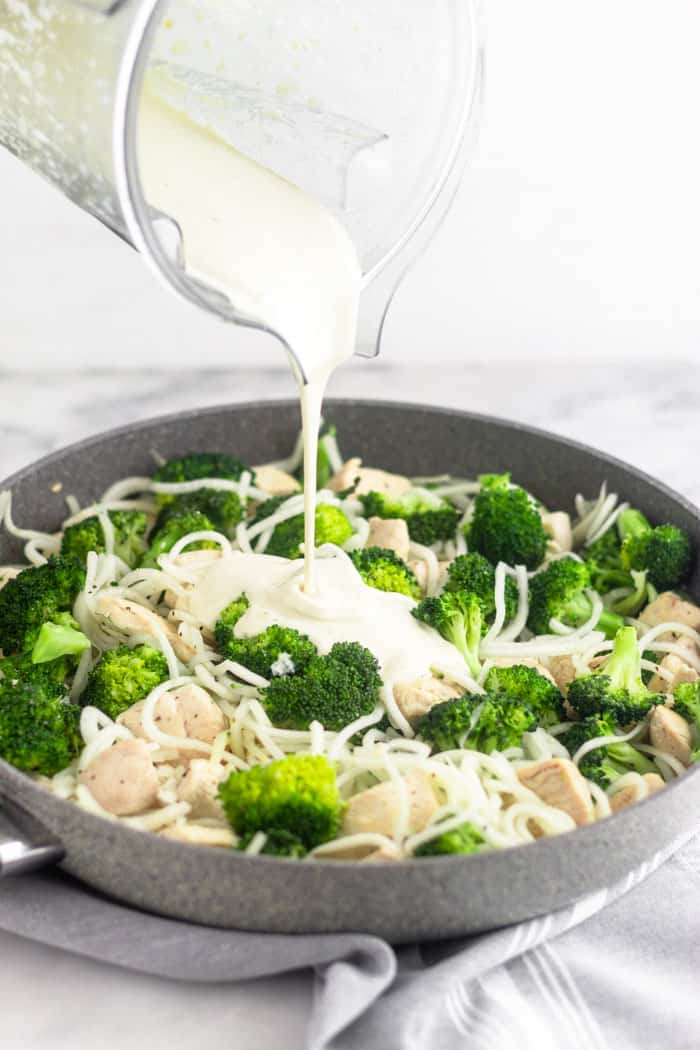 Large grey skillet filled with Whole30 chicken and broccoli. A blending is pouring dairy free Alfredo sauce over it.