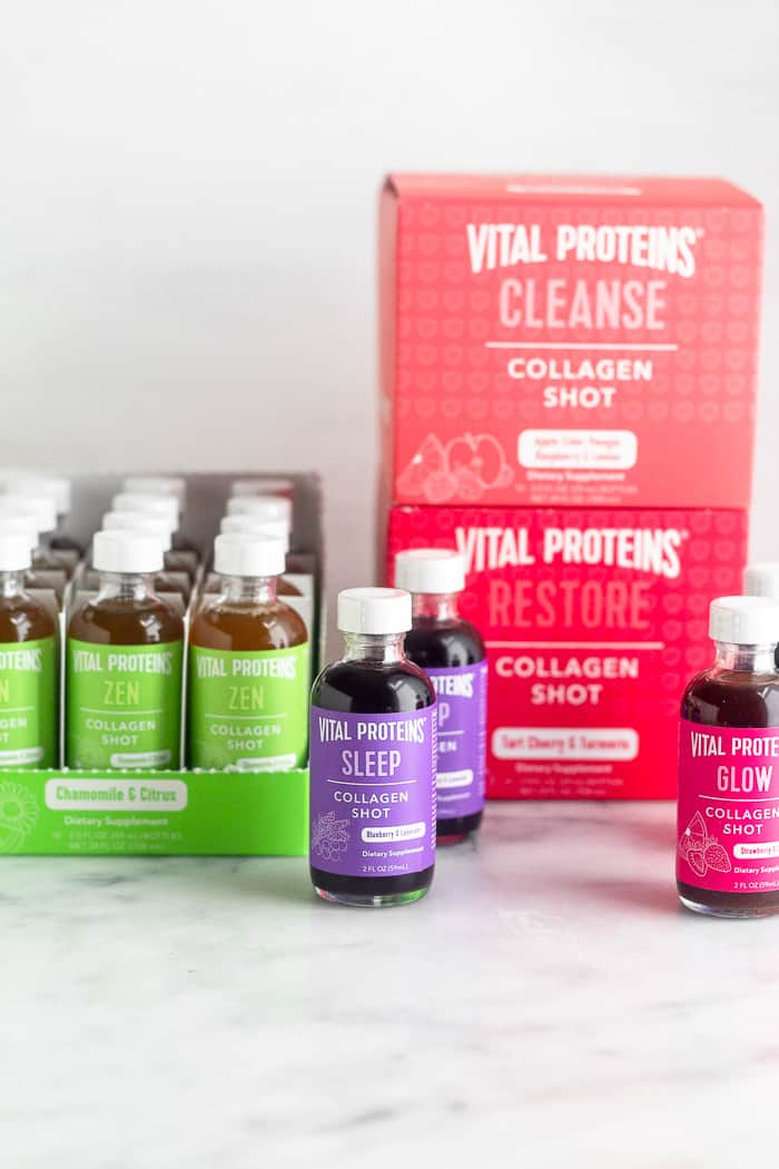 Three boxes full of collagen shots, one of them being open so you can see inside of it. Three more bottles are sitting around the boxes. There are five different flavors in total.
