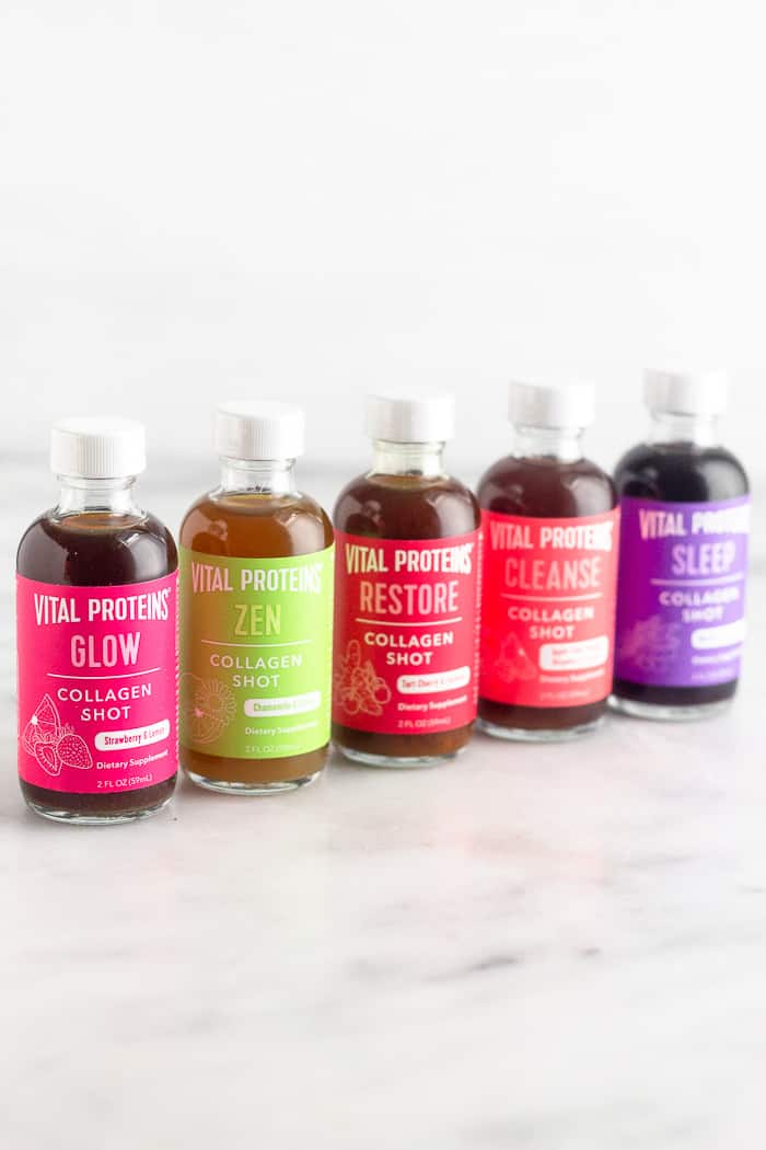 Five different flavors of collagen shits in a diagonal line on a white counter top.