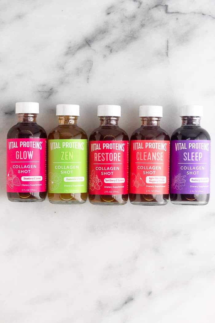 Five different flavors of collagen shots laying down next to each other on a white counter.