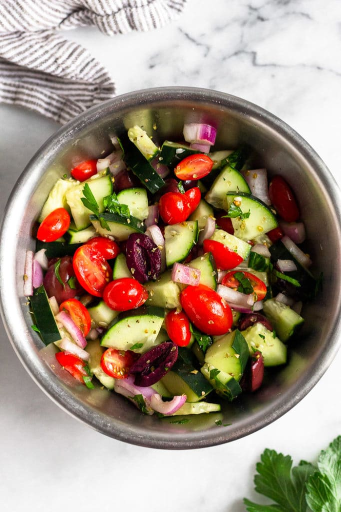 Bowl of chopped cucumber, tomatoes, olives, red onion, and parsley coating in dressing.