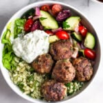 Greek bowl full of cauliflower rice, greek lamb meatballs, greek salad, lettuce, and tzatziki. Next to it is another bowl and half a juiced lemon.