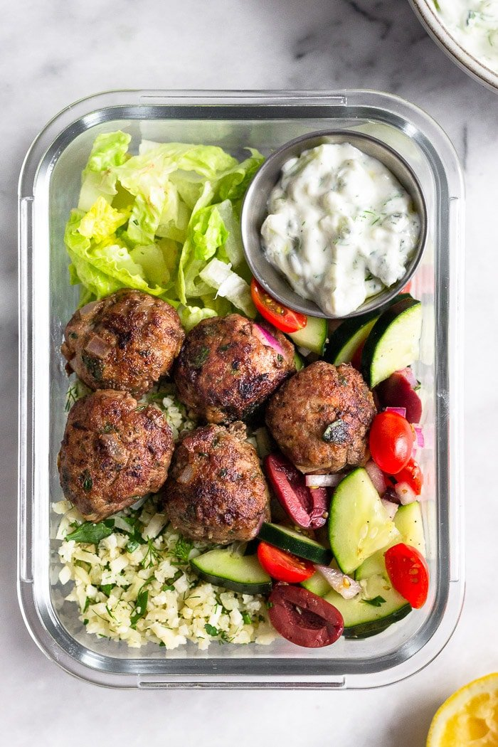 Glass meal prep container filled with chopped romaine, cauliflower rice, greek salad, lamb meatballs, and a container of tzatziki.