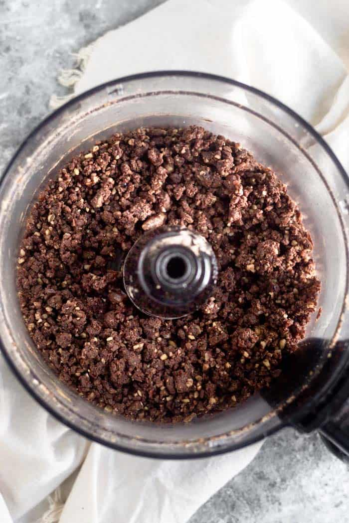 Food processor filled with walnuts and dates that have been broken down into small pieces.