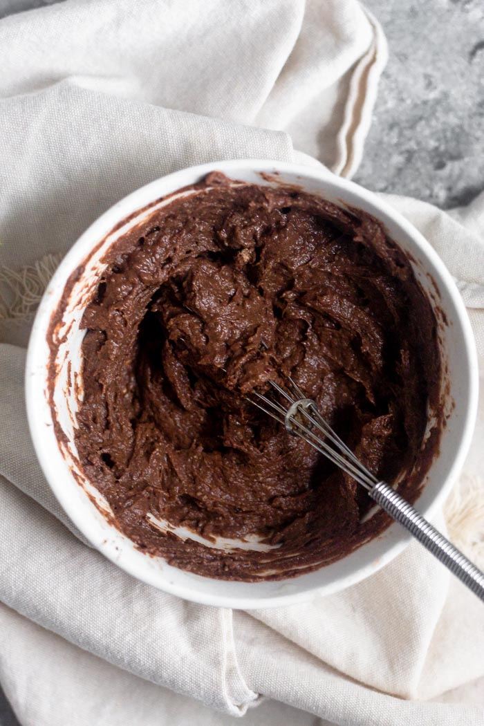 A small bowl of chocolate protein frosting with a small whisk coming out of it.