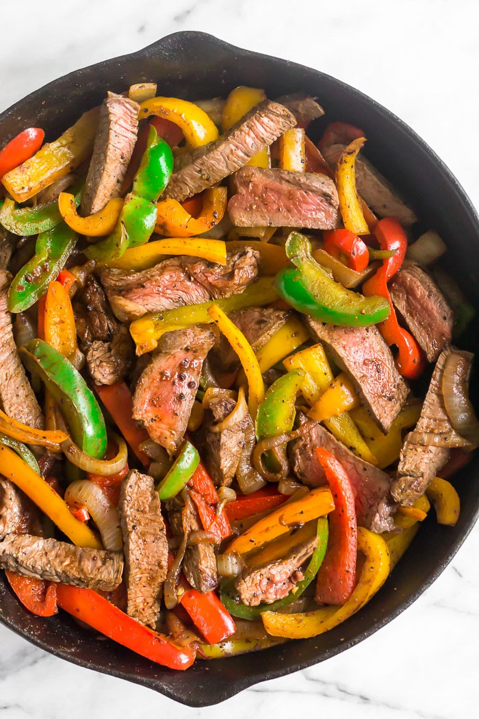 Cast iron filled with steak fajitas.
