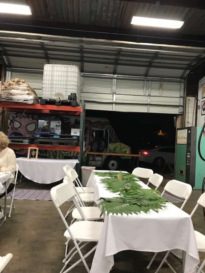 Back of a brewery with tables set up with palms on top of them. A large garage door is open with a door truck in the back.