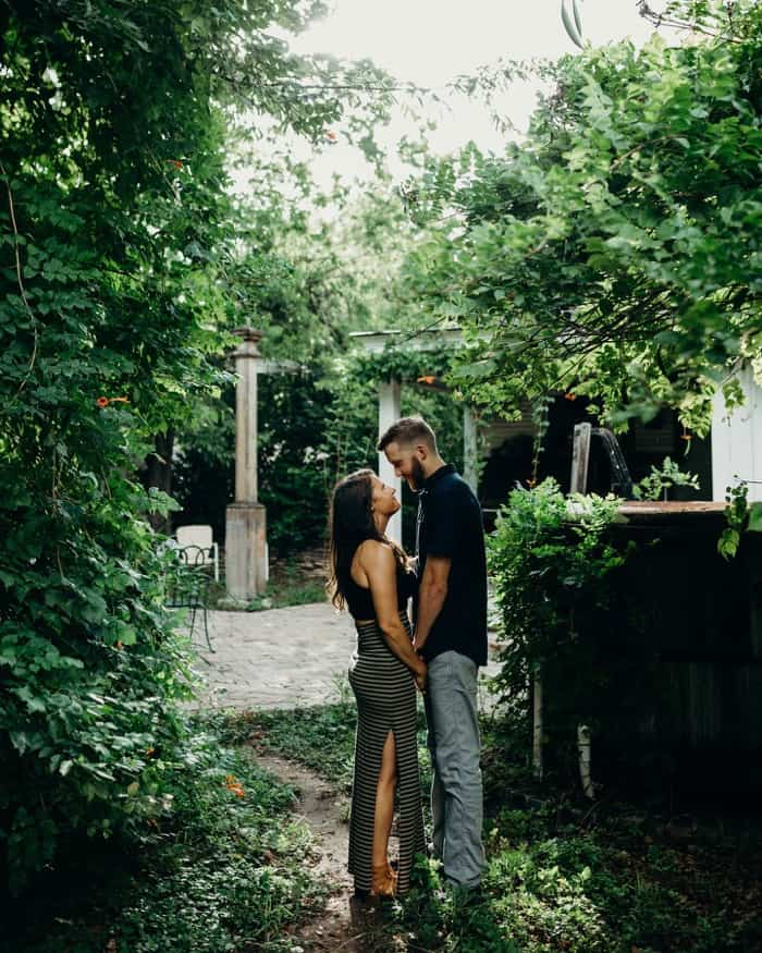 An engaged couple standing in some greenery holding hands and embracing each other.