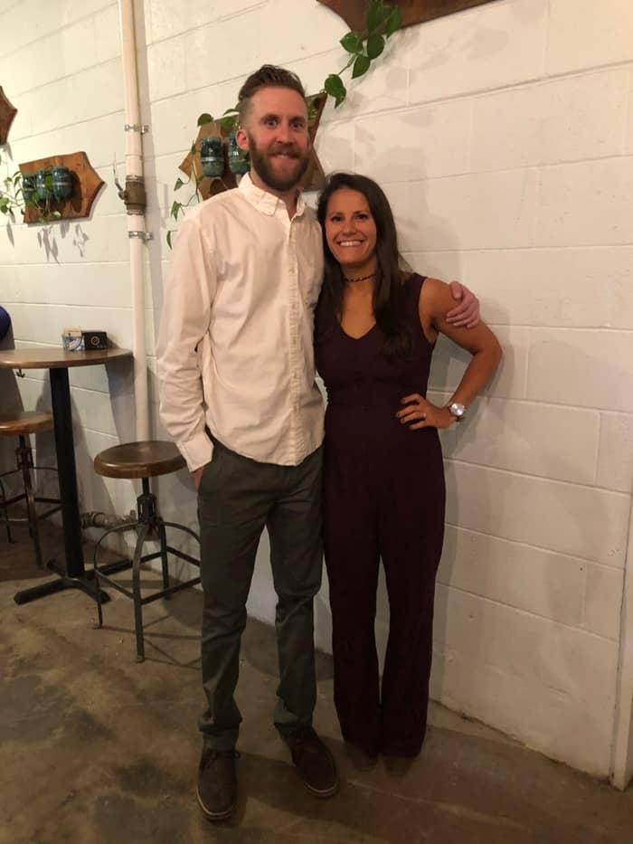 Couple at their rehearsal dinner posing for a picture. Girl has dark long hair and is wearing a jumpsuit. The guy has short brown hair and wearing a white collar shirt.