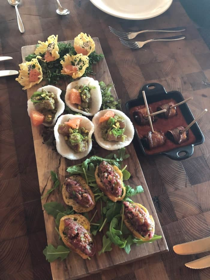 Wooden serving board filled with 3 different appetizers. Next to it is a small cast iron filled with sauce and bacon wrapped dates.