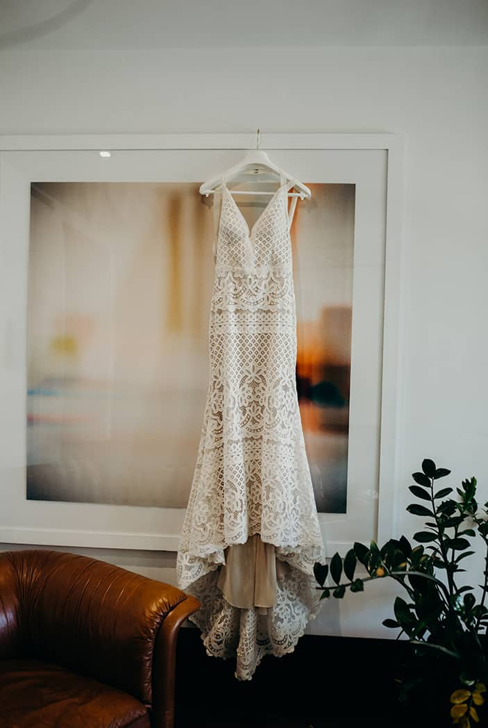 Boho lace wedding dress having up on an abstract painting. Next to it is a plant.