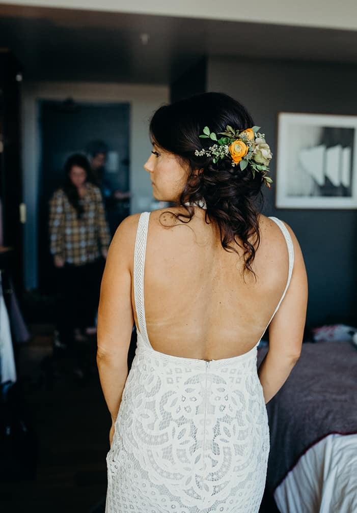 A bride wearing an open back boho wedding dress with her hair pulled back in a messy bun with flowers in it.