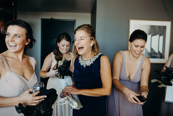 A mother laughing as her daughter is getting ready for her wedding.