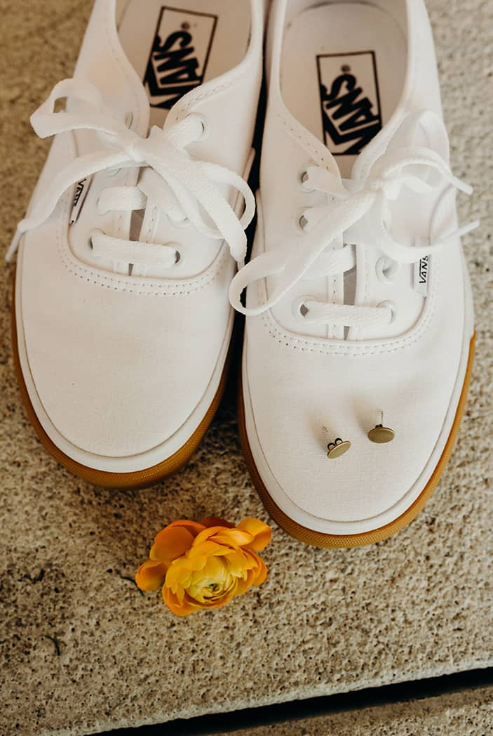 White vans with gold studs sitting on top of them. Next to them is an orange flower.