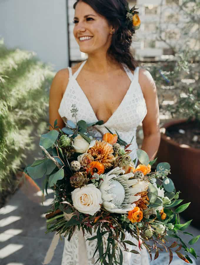 Portrait of a woman in her wedding dressing smiling holding a large bouquet of flowers.