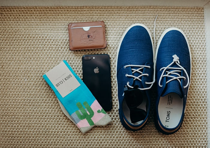 Men's blue TOMs, a pair of socks with a cactus on it, an iPhone, and a leather wallet.