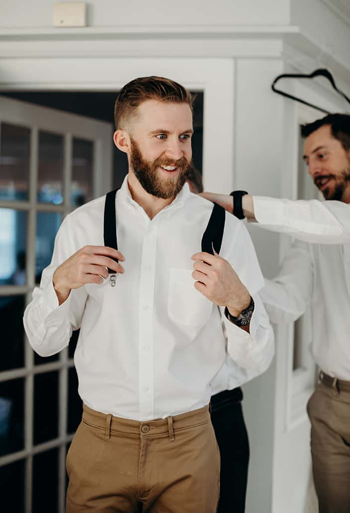 A groom getting ready for his wedding with his friend helping put on his suspenders.