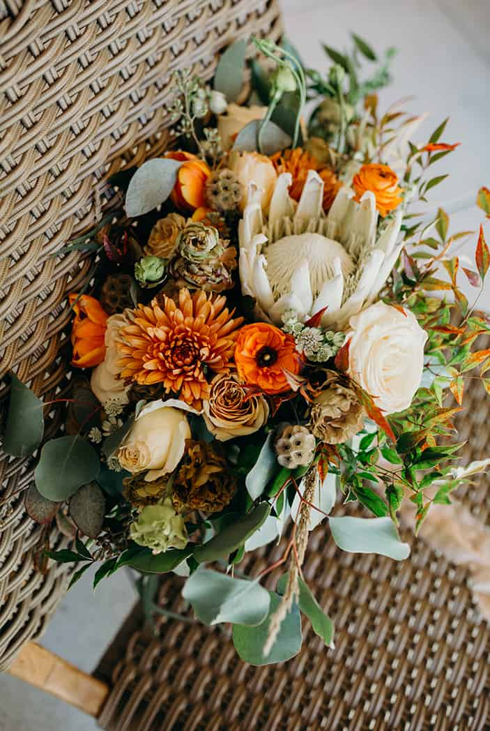 A large bouquet of wedding flowers consisting of whites, oranges, and greens.