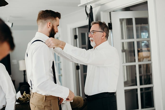 A son getting ready for his wedding with his dad helping put on his suspenders.