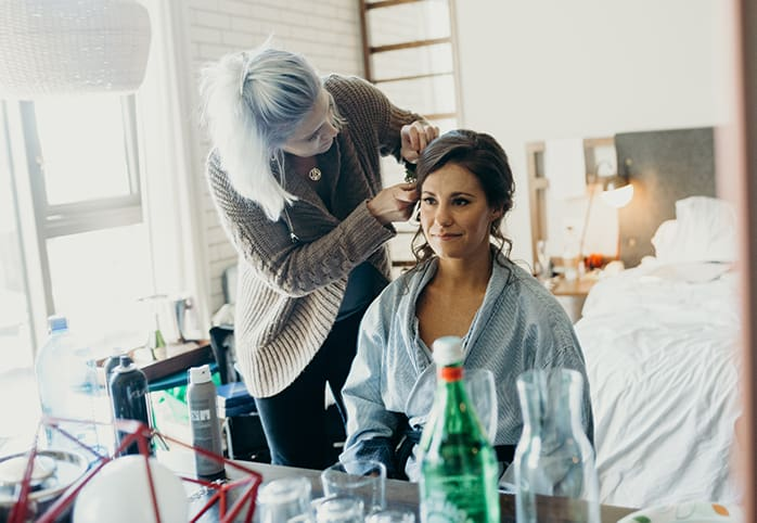 A bride getting her hair done on her wedding day.