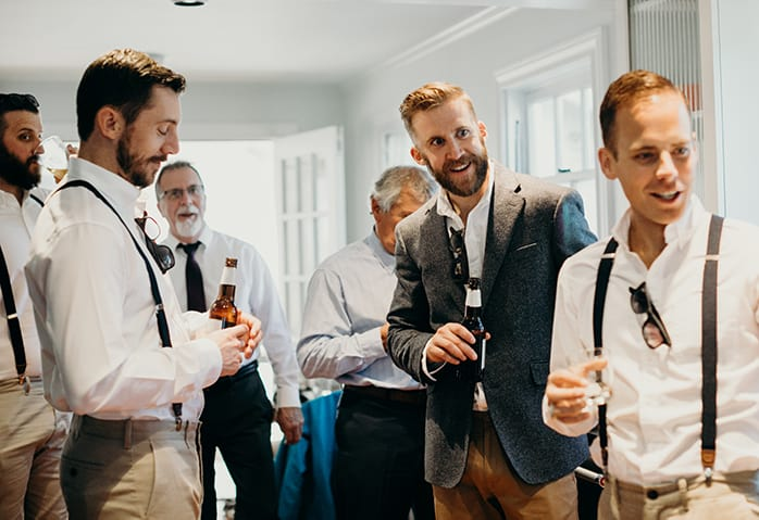 A group of guys, including the groom, getting ready for a wedding with beers in their hand.