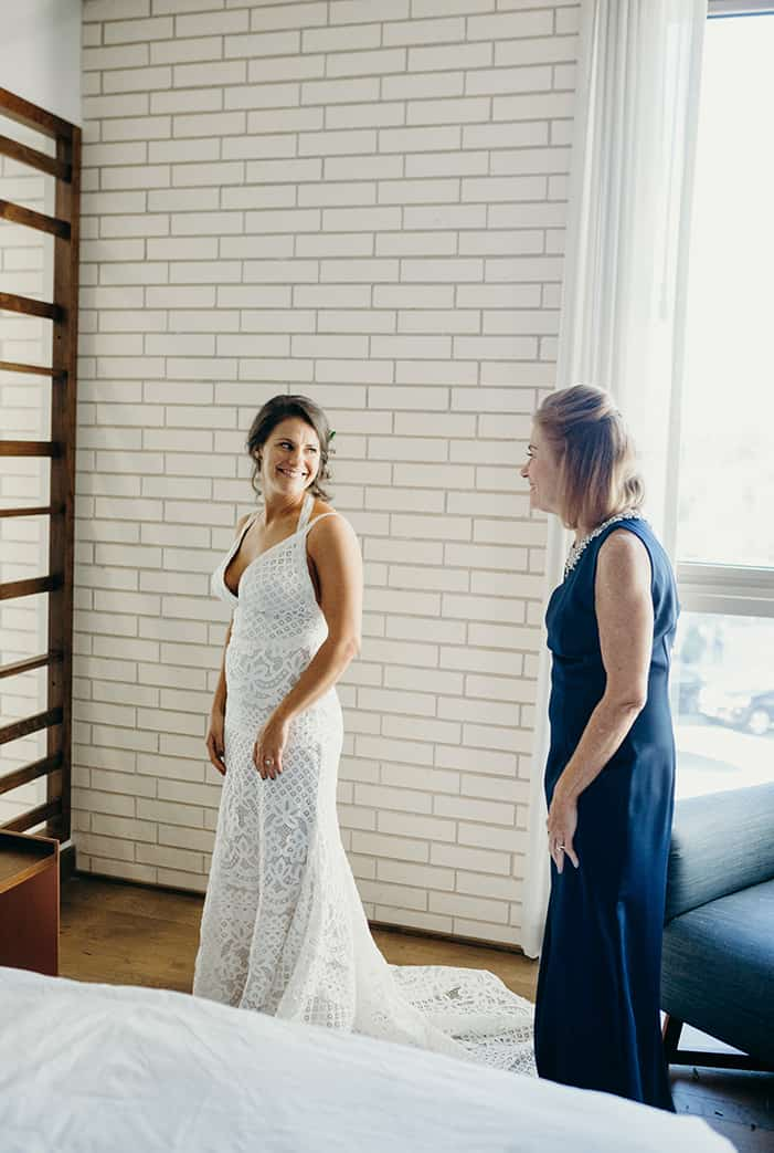 A bride in her dress turning to see her mom for the first time while getting ready in a hotel room.