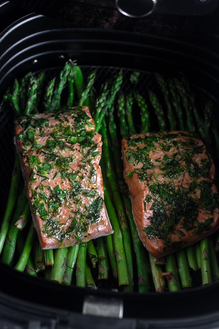 Two dill coated salmon over top asparagus in an air fryer basket