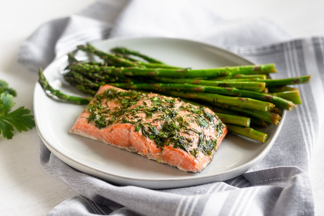 One pan salmon & asparagus made in the air fryer on a white plate sitting on a grey towel.