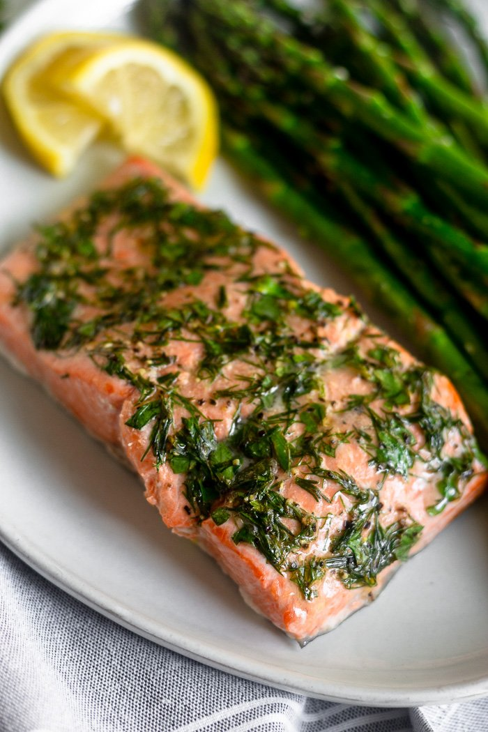 A close up of dill coated salmon and asparagus with two lemon wedges on a white plate.